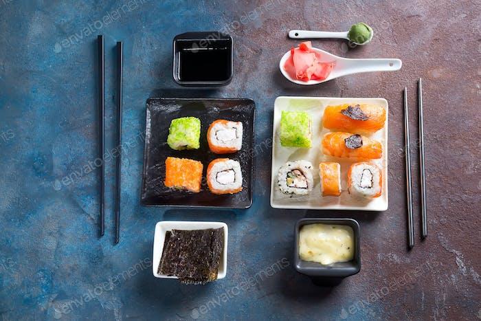 Traditional Japanese food- sushi, rolls, chopsticks, soy sauce on duotone slate background. Sushi