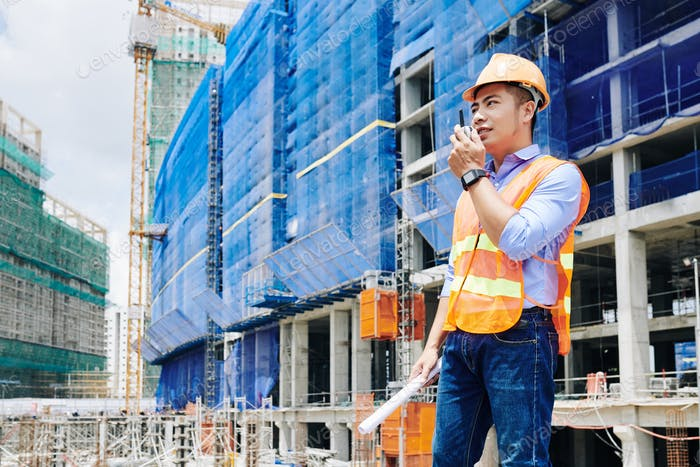 Contractor using walkie-talkie for communication