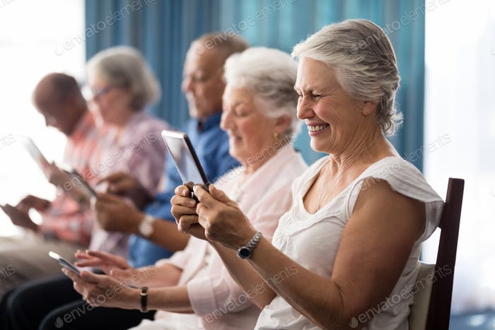 Row of smiling senior people sitting on chairs using digital tablets