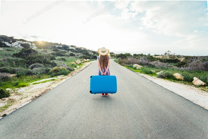 Back view of woman with blue suitcase on a road