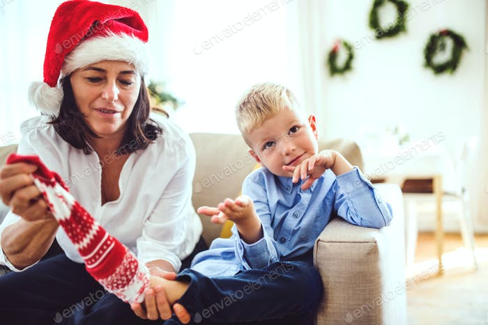 A small boy and grandmother with a Santa hat sitting on a sofa at home at Christmas time.