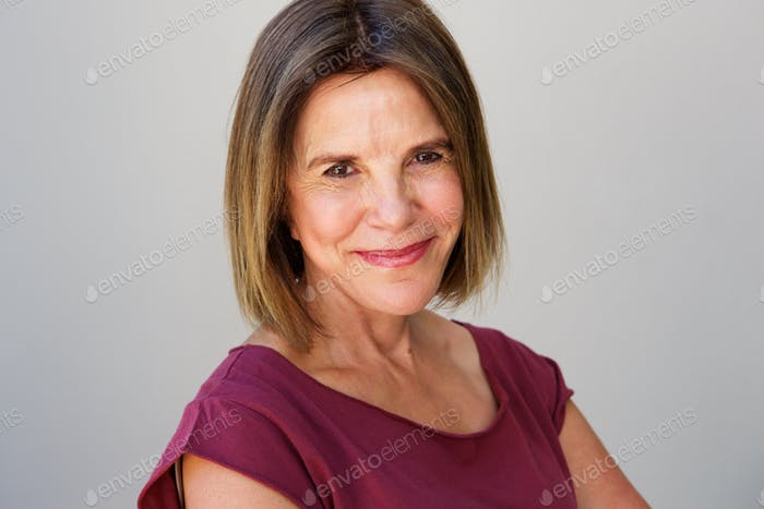 smiling elderly woman against gray wall