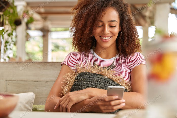 Positive dark skinned woman browses internet on modern smart phone, holds gadget in hand, laughs whi