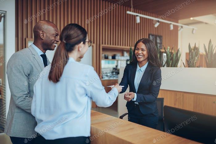 Lächelnde Gäste geben ihre Check-in-Informationen an die Hotelrezeption