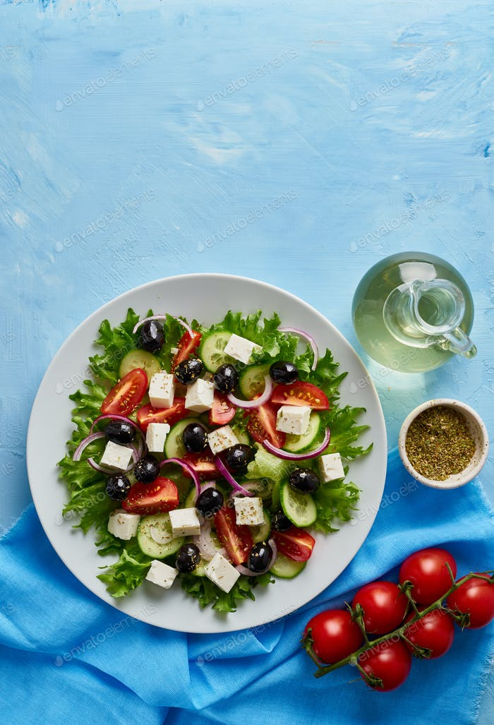 Greek salad on white plate on bright blue table, top view, copy space