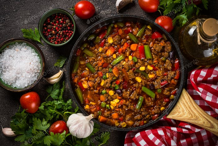 Chili con carne in skillet on dark stone table