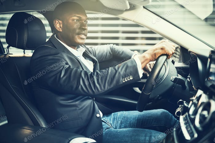 Smiling African businessman driving his car through city streets