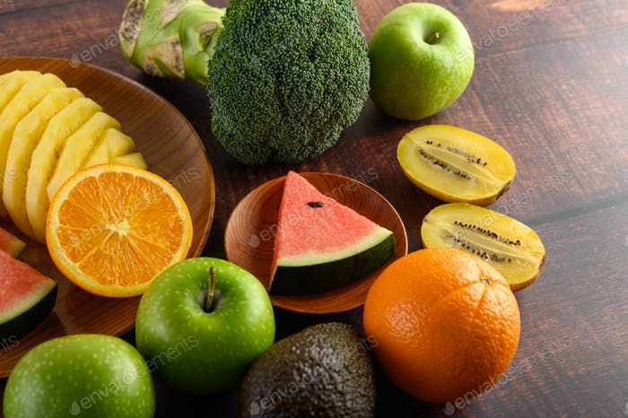 Watermelon, orange, pineapple, kiwi cut into slices with apples and broccoli on a wooden plate.