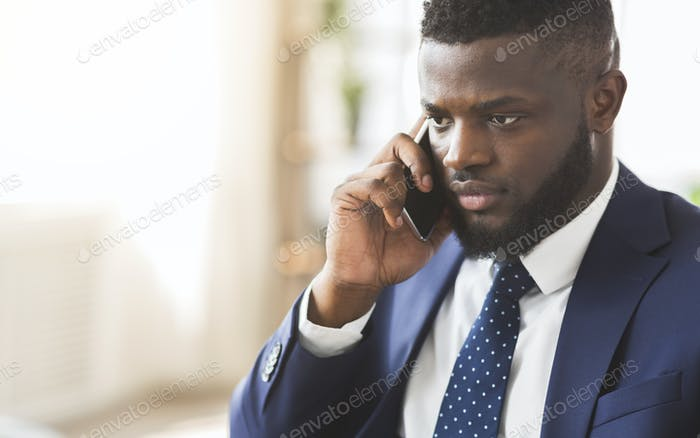 Handsome angry businessman talking by smartphone with employees