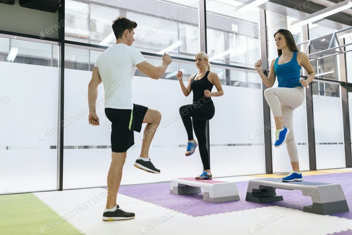 Personal trainer exercising with trainees