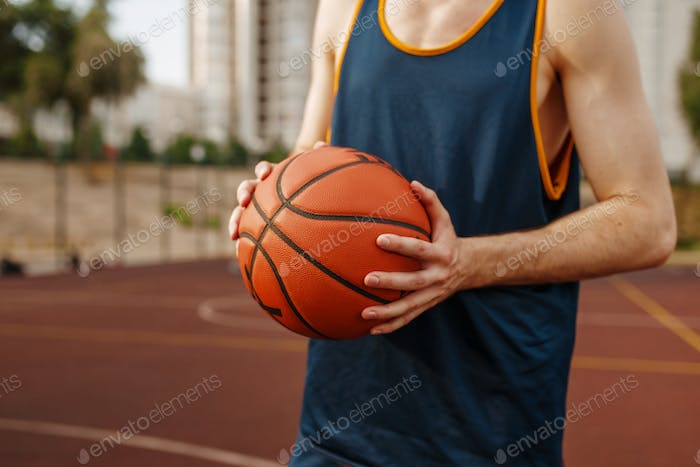 Basketball player aiming for throw, outdoor court