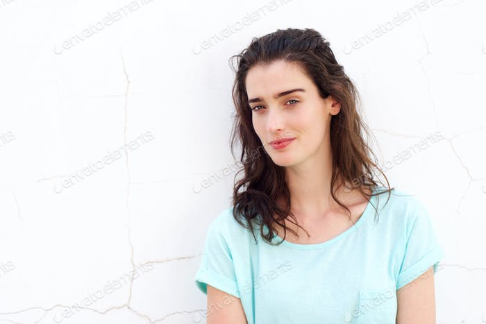 Attractive young woman against white wall