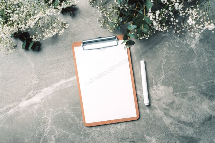 Feminine workspace with notebook, clipboard, paper, pink peony, eucalyptus flower on marble