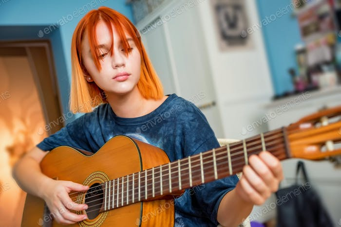 Pretty red-haired teenage girl plays guitar in her room