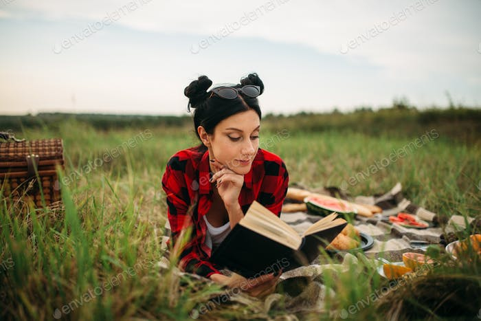 Young woman lies on plaid and reads book, picnic