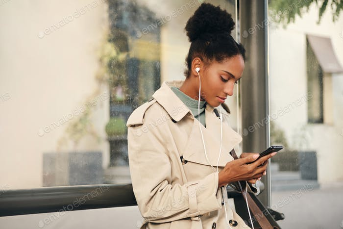 African American girl in stylish trench coat and earphones dreamily using cellphone at bus stop