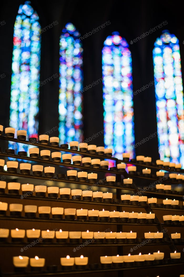 Rows of firing candles in catholic church
