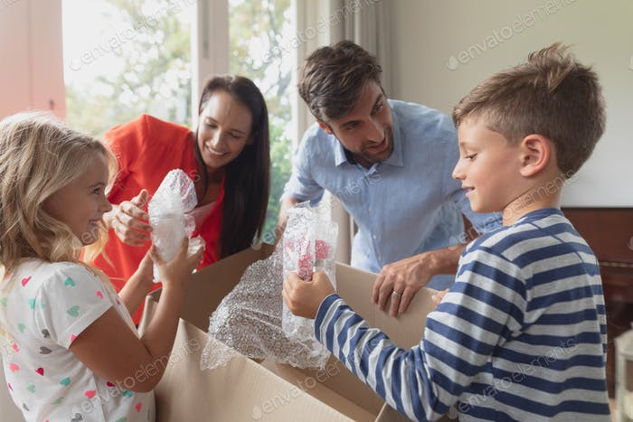 Front view of Caucasian family unpacking cardboard box in living room at home