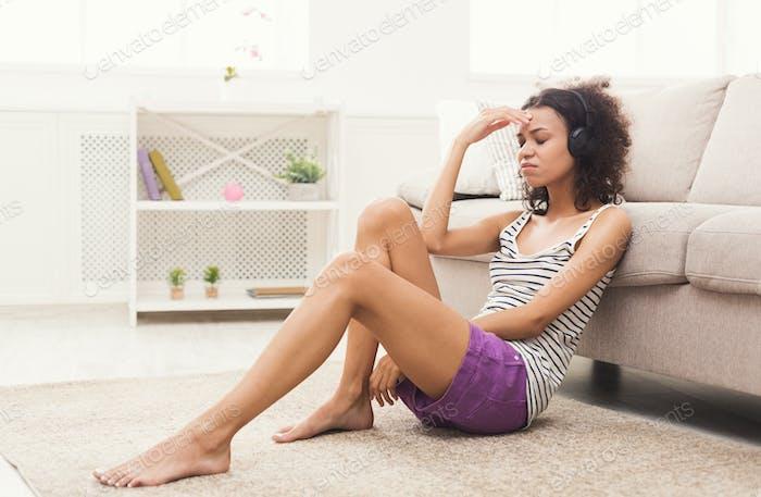 Young sad woman in headphones on floor