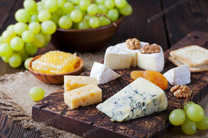 Assortment of cheese with honey, nuts and grape on a rustic cutting board
