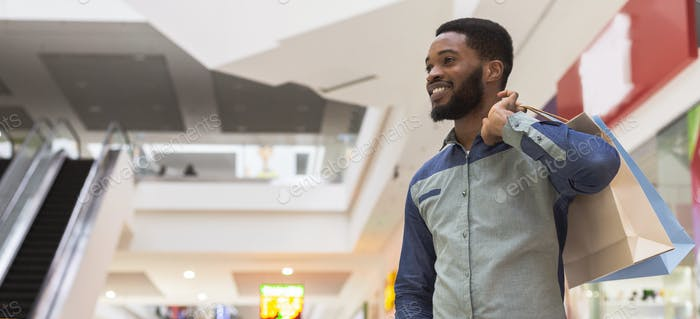 Satisfied african guy with paper bags looking at copy space