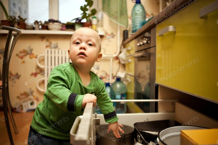 Curious child opens kitchen drawer with dishes
