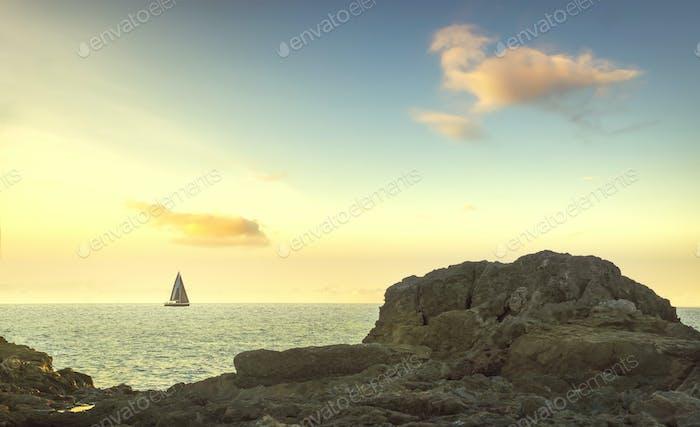 Sailboat on the sea and rocks in Castiglioncello at sunset. Rosignano, Tuscany, Italy