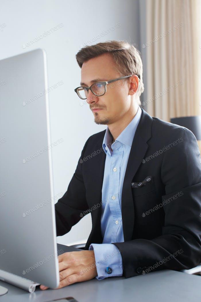 Hübscher Geschäftsmann, der mit Computer arbeitet.