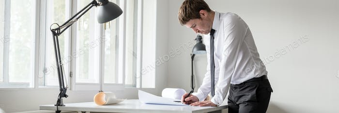 Wide panorama view of a designer using pencil while working at t