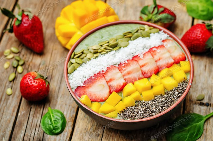 Spinach smoothie bowl with strawberries, coconut, mango, pumpkin