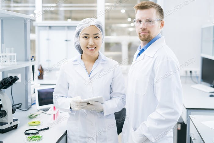 Smiling microbiologists standing in laboratory with tablet