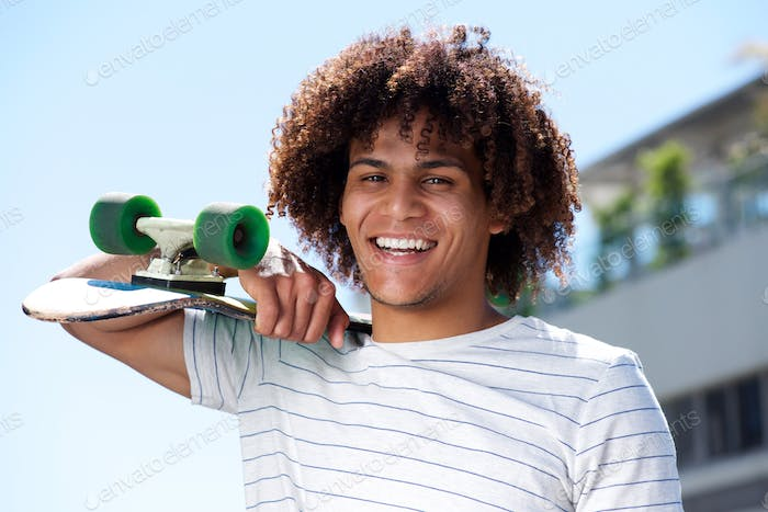 happy young guy smiling outside with skateboard
