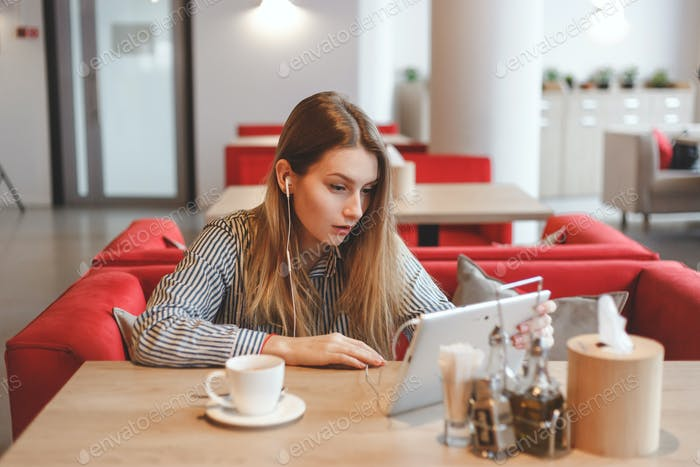 Surprised armenian girl in cafe using tablet