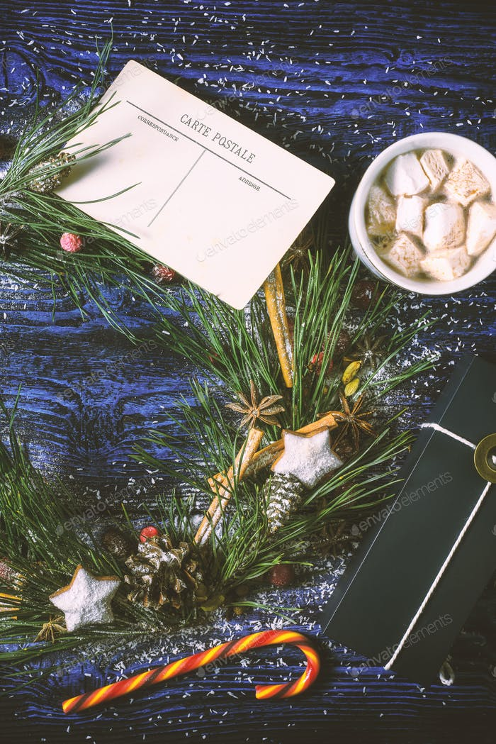 Christmas wreath with postcard and present on the wooden background  vertical