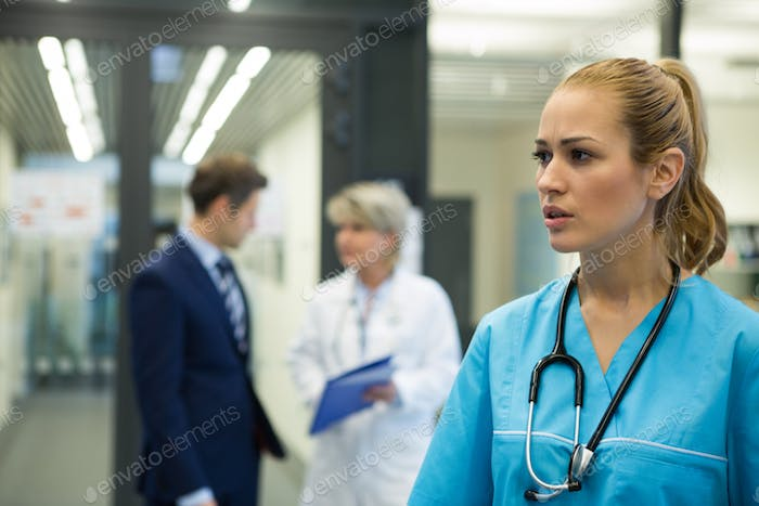 Thoughtful female doctor standing n corridor