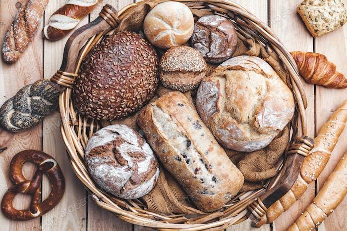 Una cesta llena de delicioso pan fresco sobre Fondo de De madera