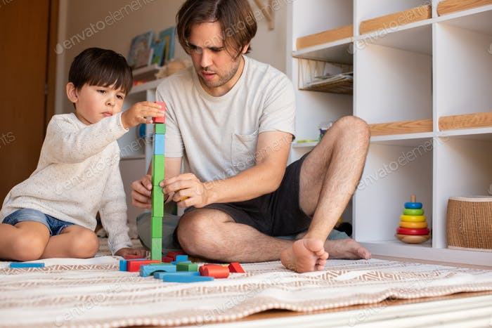 kid and his father playing at home with wood building blocks. Homeschooling. Stay at home.
