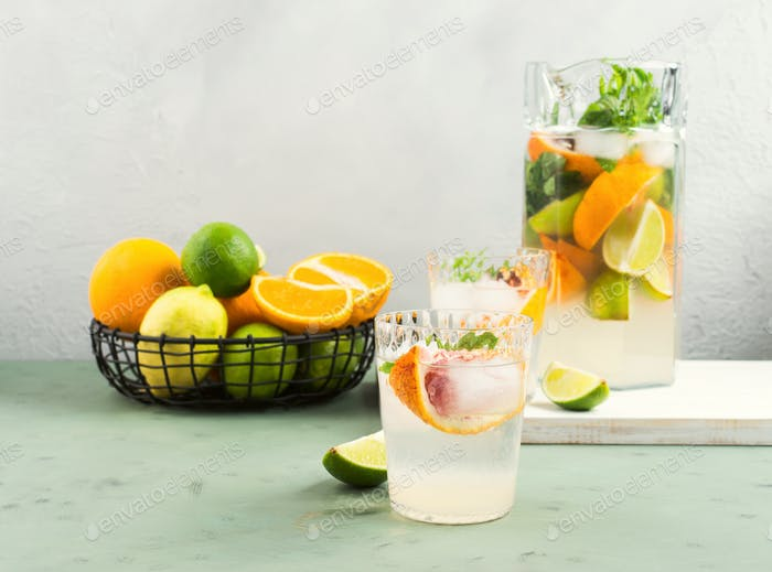 Fresh summer citrus drink with ice on green