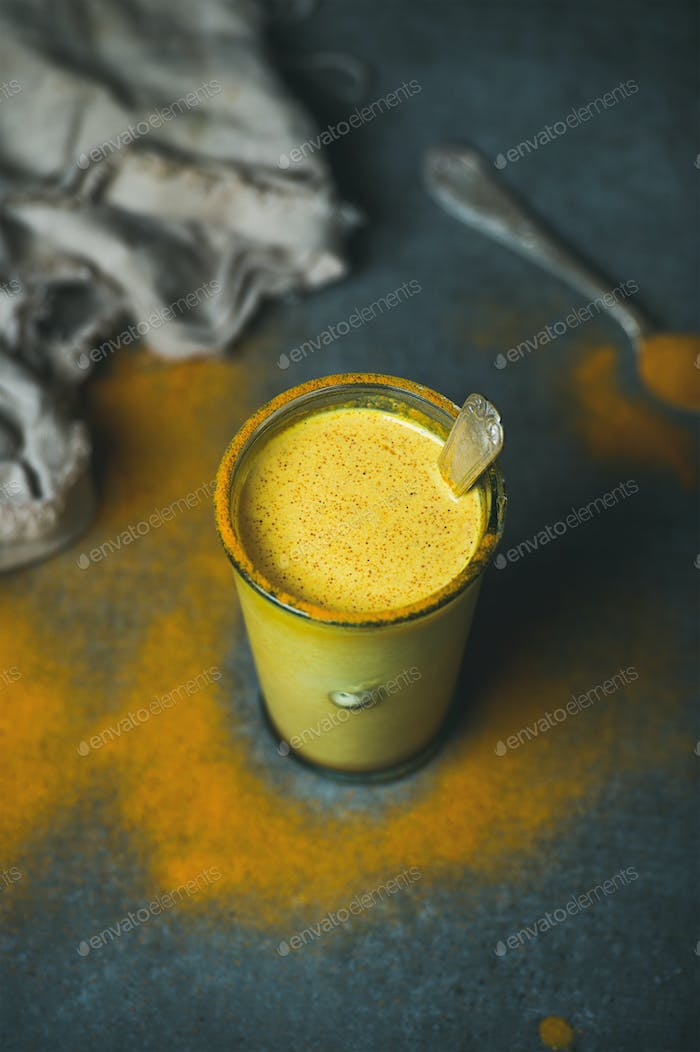 Golden milk with turmeric powder in glass, selective focus