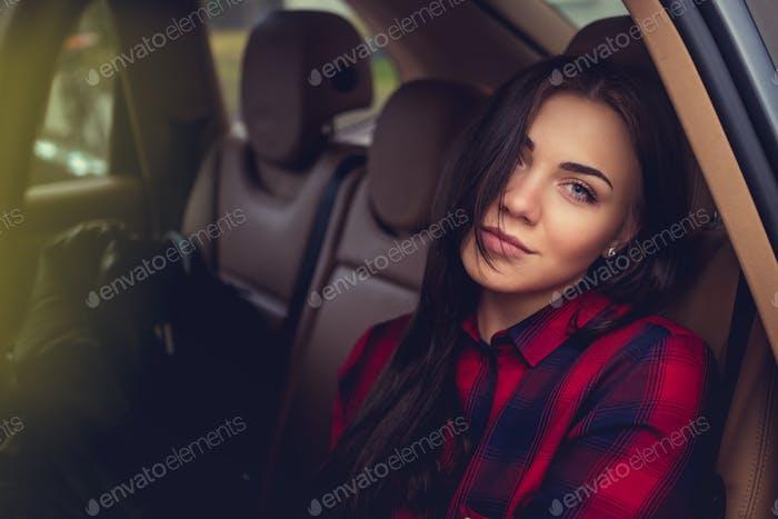 Brunette girl in a car.