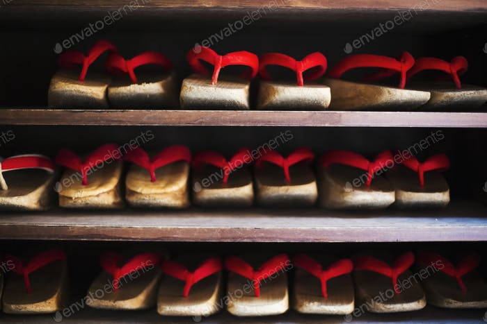 Rows of traditional wooden sandals with thick soles and red straps worn by geisha, okobo or geta.