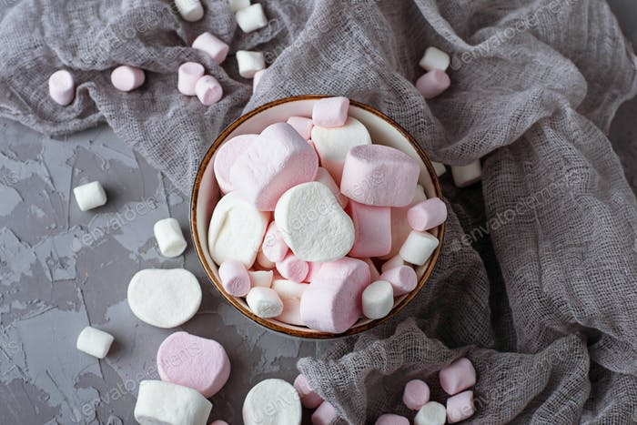 White and pink marshmallows on gray concrete background