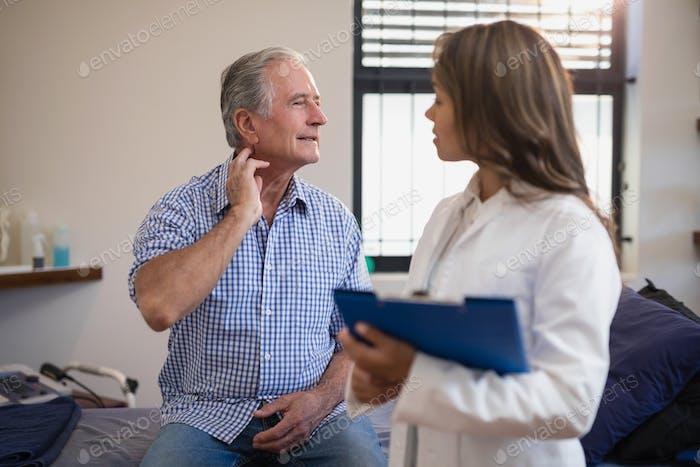 Senior male patient showing neck sprain to female doctor with file