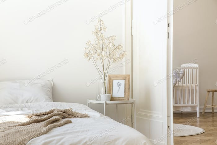 White metal bedside table with coffee mug, twig in glass vase an