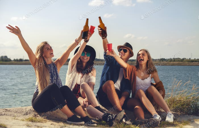 Friends having fun and drinking at the beach, positive mood