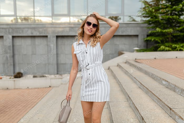 young attractive stylish woman with blond hairstyle walking in city