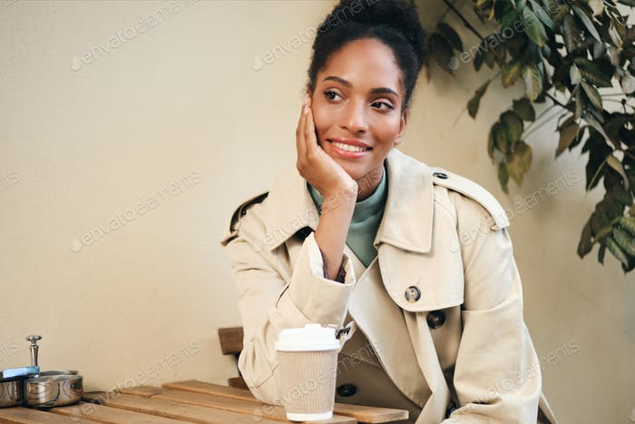 African American girl in stylish trench coat happily looking away drinking coffee in street cafe