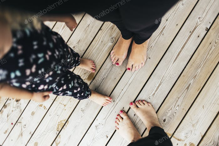 Low section of barefoot women and girl (2-3) standing