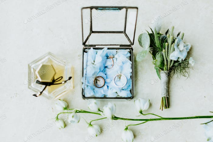 wedding ring and flowers with perfume lay flat