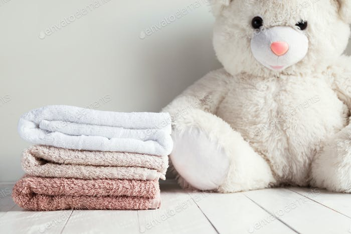 Stack of spa towels on white wooden table with white soft toy bear on background
